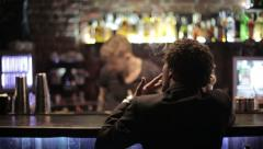A black man sitting on a bar and smokes a cigarette. HD shot with slider - stock footage