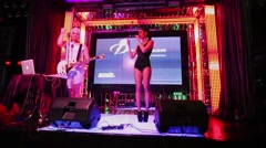 Julia Kovaleva speak on stage with guitarist Sergey Niedzwiecki Stock Footage