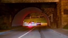 Cars and motorcycle ride under bridge on night street Stock Footage