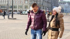 Couple hold hands and walk near Kremlin complex Stock Footage