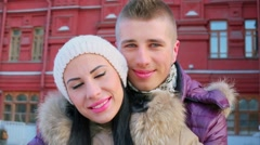 Young man kisses his girlfriend while they stand near red building Stock Footage