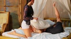 Woman beats her boyfriend by pillow on bamboo bed Stock Footage