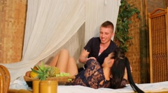 Young man make massage for his girlfriend while she lies in bed Stock Footage