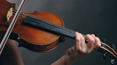 Woman playing violin over dark background Stock Footage