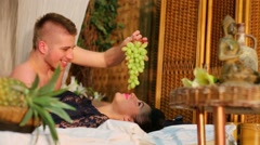 Man holds bunch of grapes above womans face while they lay on bed Stock Footage
