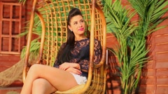 Pretty young woman sits in wicker hanging chair near beach house Stock Footage
