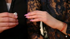 Man puts on ring on womans hand with long colorful nails Stock Footage