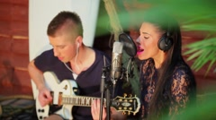 Young musician plays on guitar and woman sings in microphone Stock Footage