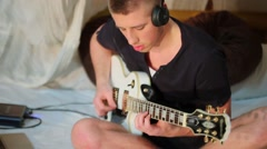Musician in headphones sits at bamboo bed and plays on guitar Stock Footage