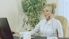 Nice blonde in the office with headphones speaks on microphone Stock Footage