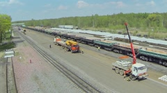 People unload sleepers from trucks with cranes Stock Footage