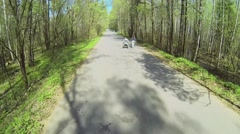 Girl walk near playmate in wheelchair on road in forest at spring Stock Footage
