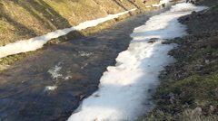 The stream in spring park flows in a frame of thawing snow. Stock Footage