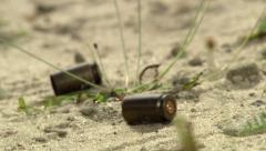 Stock Video Footage of close up of bullets falling to the ground 2