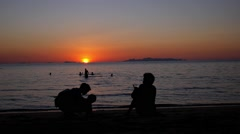Father Takes Picture of His Family Walking on The Beach at Sunset. Stock Footage