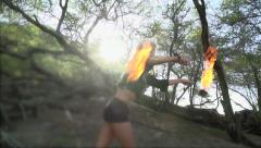 Fire dancer performs in slow motion tropical forest Stock Footage