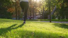 Woman running in park at sunny day, slow motion shot at 240fps, steadycam shot Stock Footage