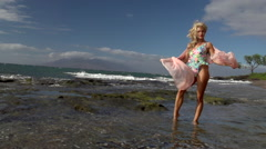 Female model in slow motion on windy beach in Maui Stock Footage