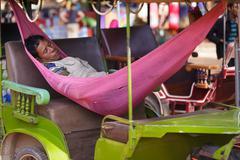 tuk tuk driver sleeping in a hammock - stock photo