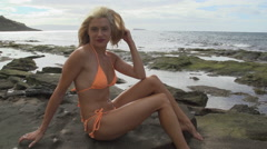 Maui swim wear model poses in orange bikini on lava rock Stock Footage