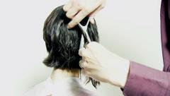 Cutting long layers of hair from the back with scissors Stock Footage