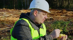 Lumberjack eating potato chips in the forest - stock footage