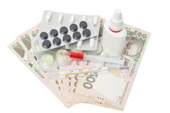 pills in a blister pack, thermometer, syringewith red liquid and nasal spray - stock photo