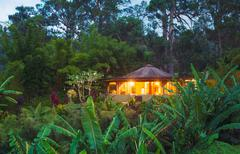 tropical home in the jungle at sunset - stock photo