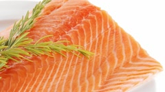 Fresh uncooked salmon fillet on plate with rosemary Stock Footage