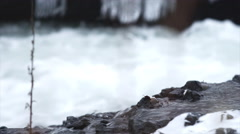Tilt up of frozen twigs in front of a rushing river Stock Footage