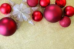 Christmas bulbs and star tree topper framing gold glitter background Stock Photos