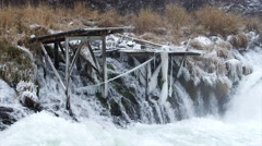 Frozen docks stand next to a rushing river in the winter Stock Footage