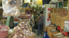 Shoppers leave open air Asian dried fish shop Stock Footage