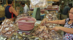 Asian fish market vendor selling dried fish heads Stock Footage