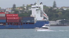 Speed boat passing container ship Stock Footage