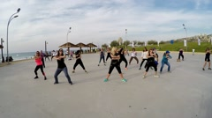 People practice Zumba near the beach Stock Footage