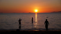 Young People Swimming in Sea at Beach on Beautiful Summer Sunset. Stock Footage