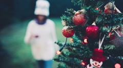 Handheld shot of teenager girl decorating a Christmas tree - stock footage