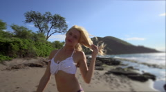 Fitness model in a bikini on a windy beach in Maui Stock Footage