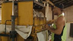 Shedhand Pressing Freshly Shorn Wool in a Woolpress Stock Footage