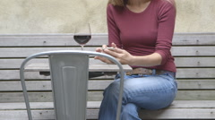 A middle aged woman texting at an outdoor table while enjoying a glass of wine Stock Footage