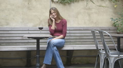 A middle aged woman talking on a cell phone at an outdoor table while enjoying a Stock Footage