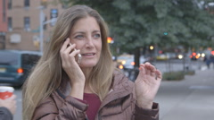 A pretty, middle aged woman talking on the telephone next to a busy Brooklyn Stock Footage