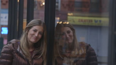 A pretty, middle aged woman leaning against a Brooklyn shop window and smiling Stock Footage