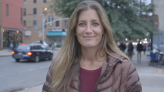 A pretty, middle aged woman smiling into the camera on a Brooklyn street - stock footage
