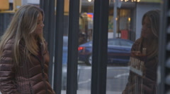 A pretty, middle aged woman looking into a Brooklyn shop window - stock footage