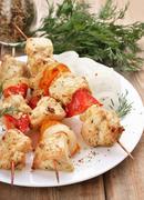 chicken shish kebab on wooden table - stock photo