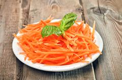 grated carrot on rustic table - stock photo