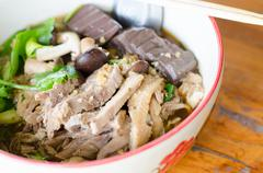 Noodles with pot-stewed duck in bowl Stock Photos