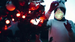 Handheld shot of teenager girl decorating a Christmas tree Stock Footage